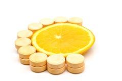 Fatia e comprimidos alaranjados da vitamina de c Imagem de Stock Royalty Free