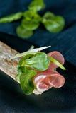 Fatia fina cor-de-rosa de presunto em uma parte de pão seco com ervas e cebolas foto de stock royalty free