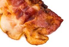 Fatia friável cozinhada de bacon isolada no fundo branco fim imagem de stock