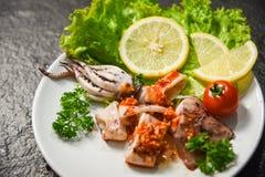 Fatia grelhada do calamar na placa no restaurante do marisco - salada do calamar com as ervas picantes e as especiarias do molho  imagens de stock royalty free