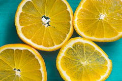 Fatias brilhantes de laranjas suculentas no fundo azul fotografia de stock royalty free