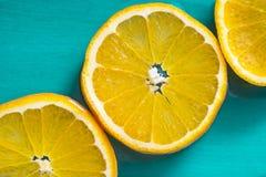 Fatias brilhantes de laranjas suculentas no fundo azul imagens de stock