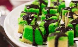 Fatias coloridas do bolo com xarope de chocolate imagens de stock