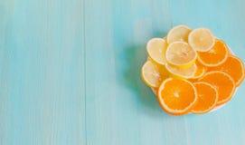 Fatias cortadas de laranja e de limão em uma placa em um close-up de madeira azul do fundo Alimento saudável do vegetariano da vi fotos de stock