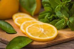 Fatias da hortelã fresca e do limão na placa de madeira Fotos de Stock