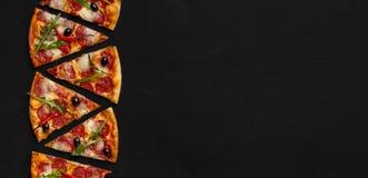 Fatias da pizza com salada do salame e de foguete no fundo preto fotografia de stock royalty free