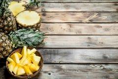 Fatias de abacaxi em uma bacia e em um abacaxi fresco imagens de stock royalty free