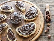 Fatias de baguette com creme do chocolate na placa de madeira Fotografia de Stock Royalty Free