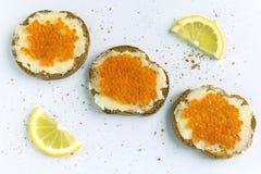 3 fatias de baguette manchadas com a manteiga e o caviar vermelho no fundo branco Configuração lisa Sanduíches e limão vermelhos  foto de stock