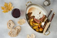 Fatias de bife com as batatas na bandeja com vinho Fotos de Stock