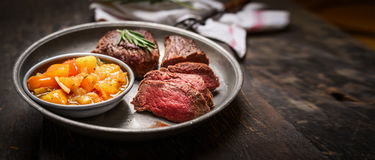 Fatias de bife roasted raro médio da carne e de molho da salsa no fundo de madeira rústico Foto de Stock Royalty Free