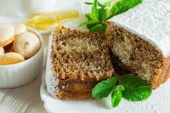 Fatias de bolo do biscoito, fatia de limão, cookies pequenas e folhas de hortelã em uma tabela de madeira branca imagem de stock