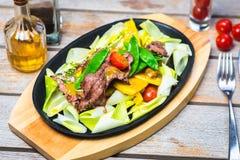 Fatias de carne com vegetais em uma bandeja quente Imagem de Stock Royalty Free
