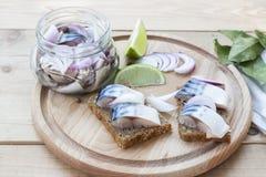 Fatias de cavala posta de conserva com cebola em um frasco, em um cal, em um louro e em um pão na placa de madeira Foto de Stock