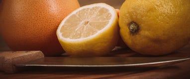 Fatias de citrino orgânico fresco com a faca na placa de madeira Imagens de Stock