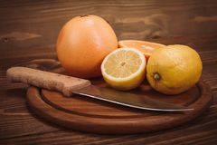 Fatias de citrino orgânico fresco com a faca na placa de madeira Imagens de Stock Royalty Free