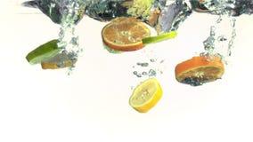 Fatias de laranjas, de cais e de limões caindo na água no movimento lento super vídeos de arquivo