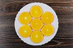 Fatias de laranjas maduras no prato branco na tabela de madeira Fotografia de Stock Royalty Free