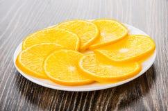 Fatias de laranjas maduras no prato branco na tabela escura Imagem de Stock