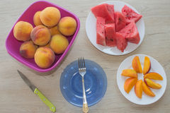 Fatias de melancia e de pêssegos em uma placa na tabela de madeira Imagens de Stock Royalty Free