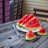 Fatias de melancia e de uma faca em uma placa em um backgrou de madeira Foto de Stock