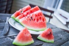 Fatias de melancia e de uma faca em uma placa em um backgrou de madeira Foto de Stock Royalty Free