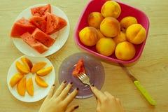 Fatias de melancia e de pêssegos em uma placa na tabela de madeira Fotografia de Stock Royalty Free