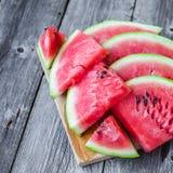 Fatias de melancia em uma placa em um fundo de madeira Fotos de Stock Royalty Free