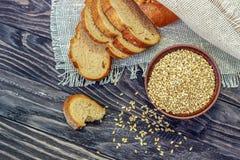 Fatias de pão do inteiro-trigo com sementes do trigo em um backgro de madeira fotografia de stock