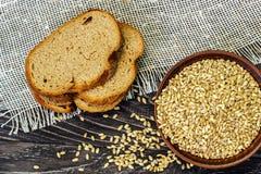 Fatias de pão do inteiro-trigo com sementes do trigo em um backgro de madeira imagem de stock
