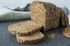 Fatias de pão de mistura inteiro da grão com semente de girassol, em uma placa de corte cinzenta fotografia de stock
