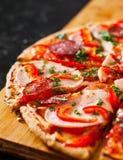 Fatias de pizza com mozzarella, presunto, tomates, salame, pimenta, especiarias dos pepperoni e manjericão fresca Foto de Stock Royalty Free