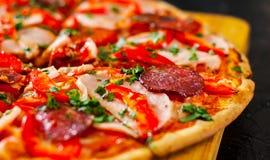 Fatias de pizza com mozzarella, presunto, tomates, salame, pimenta, especiarias dos pepperoni e manjericão fresca Imagem de Stock