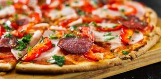 Fatias de pizza com mozzarella, presunto, tomates, salame, pimenta, especiarias dos pepperoni e manjericão fresca Foto de Stock