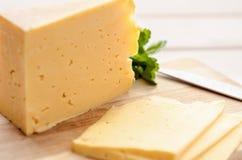 Fatias de queijo em uma placa de corte com Fotografia de Stock