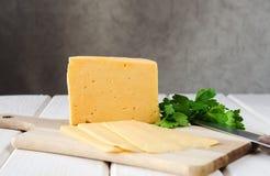 Fatias de queijo em uma placa de corte com Foto de Stock