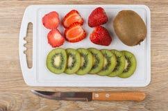 Fatias de quivi e de morango na placa de corte, faca de cozinha Imagens de Stock