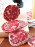 Fatias de salame italiano na placa de desbastamento Fotografia de Stock