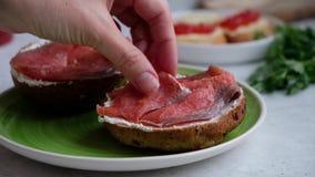 Fatias de salmões vermelhos em um pão escuro do sésamo com queijo creme, movimento lento dos lugares da mão de um cozinheiro chef vídeos de arquivo