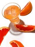 Fatias de toranja suculenta e de um vidro da limonada fresca com gelo em um fundo branco imagens de stock royalty free