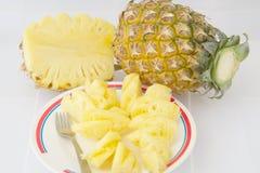 Fatias do abacaxi na placa com a forquilha no fundo branco Fotografia de Stock Royalty Free