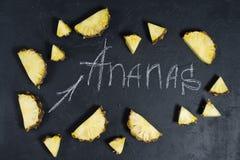 Fatias do abacaxi no fundo preto com espa?o para o texto e a inscri??o do giz foto de stock