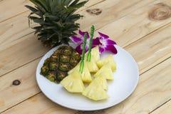 Fatias do abacaxi no prato branco na madeira imagem de stock