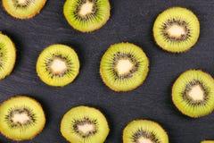 Fatias do fruto de quivi no fundo preto da ardósia Foto de Stock