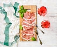 Fatias do presunto de Parma dos di do Prosciutto e vidros de vinho cor-de-rosa Imagens de Stock Royalty Free