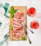 Fatias do presunto de Parma dos di do Prosciutto e vidros de vinho cor-de-rosa Fotos de Stock Royalty Free