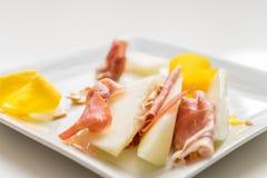 Fatias do Prosciutto com o limão amarelo na placa branca com sementes imagens de stock royalty free