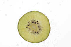 Fatias do quivi na água com bolhas Imagens de Stock