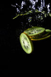 Fatias do quivi no respingo da água Imagem de Stock Royalty Free