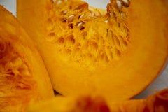 Fatias dos vegetais saborosos e saudáveis - abóbora brilhante e alaranjada suculenta com as sementes na tabela fotos de stock royalty free